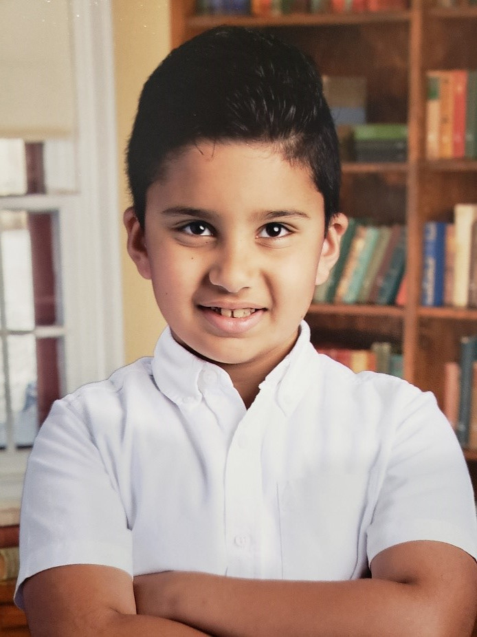 Ali Zaben, 9, poses for a school picture. He's smiling and crossing his arms.