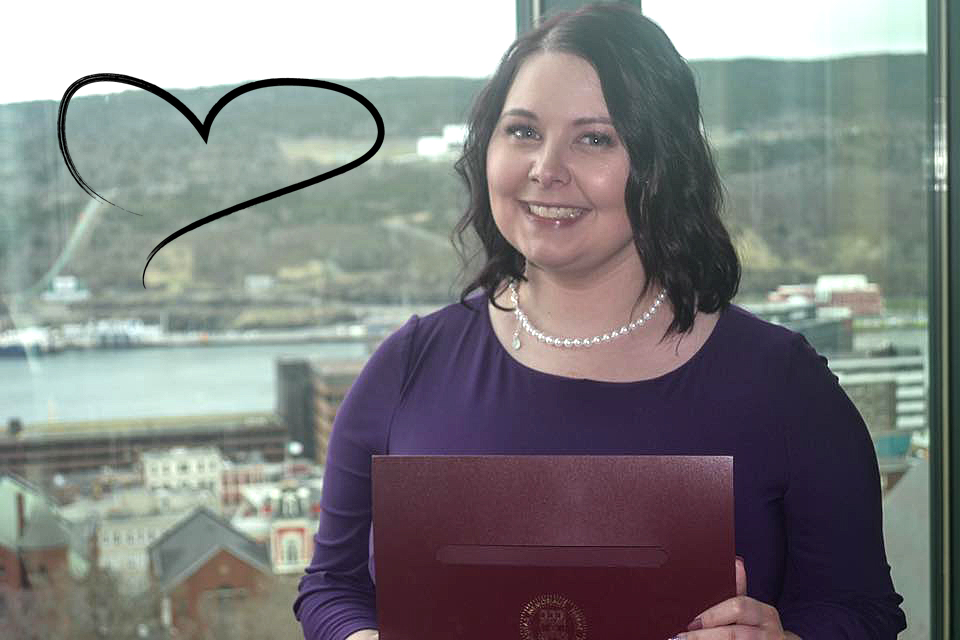 Brittany Farrell, smiling for the camera, standing in front of a window that overlooks the city of St. John's, Newfoundland. A heart graphic can be seen against the window.