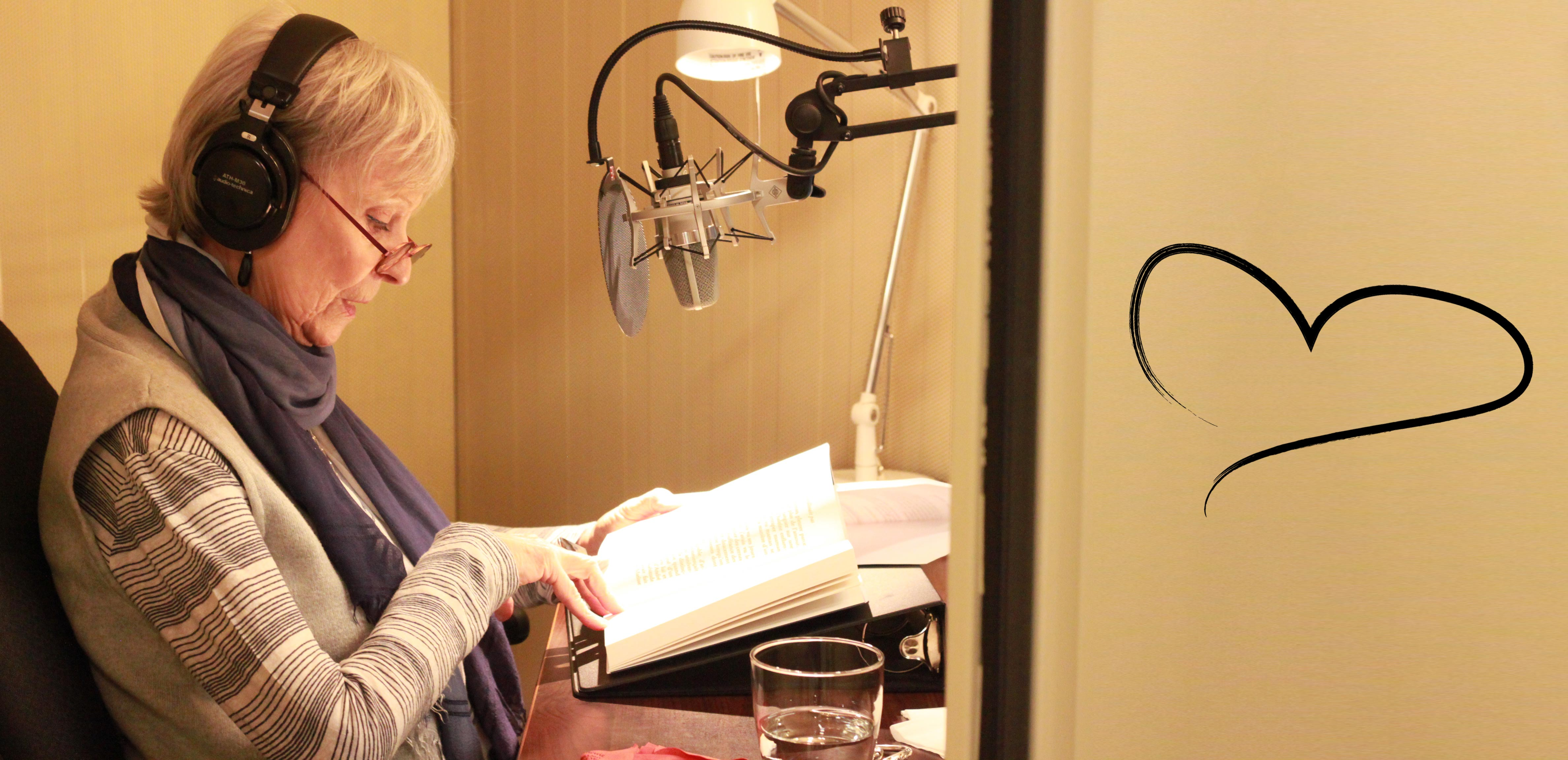 Celine Garneau, reading from a book in one of CNIB's recording studios. A heart graphic can be seen on the wall in the right side of the picture