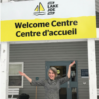 Sherri Helsdingen stands in front of the CNIB Lake Joe Welcome Centre sign.