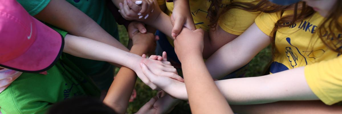 A pile of hands packed on top of one another in a group circle.