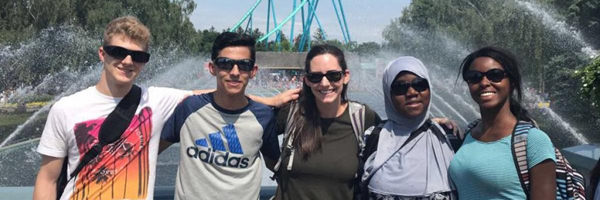 A group of four smiling teenagers and a volunteer pose for a photo at Canada's Wonderland.