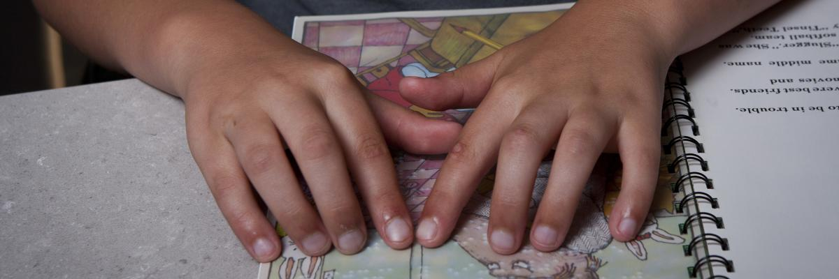 Young boy's hand reading Braille book
