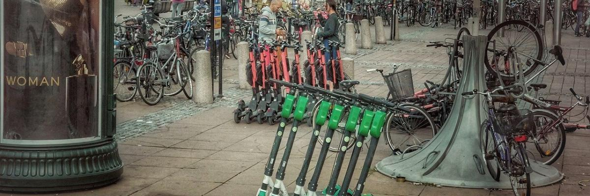 A city sidewalk with a row of electric scooters lined up on it.