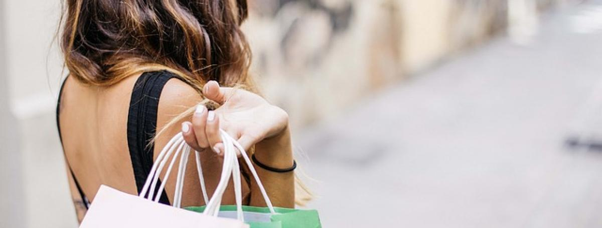 A woman slings shopping bags over her shoulder.