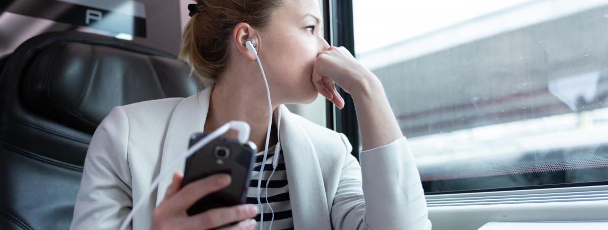 A woman has earbuds in and listens to a podcast on her smartphone.