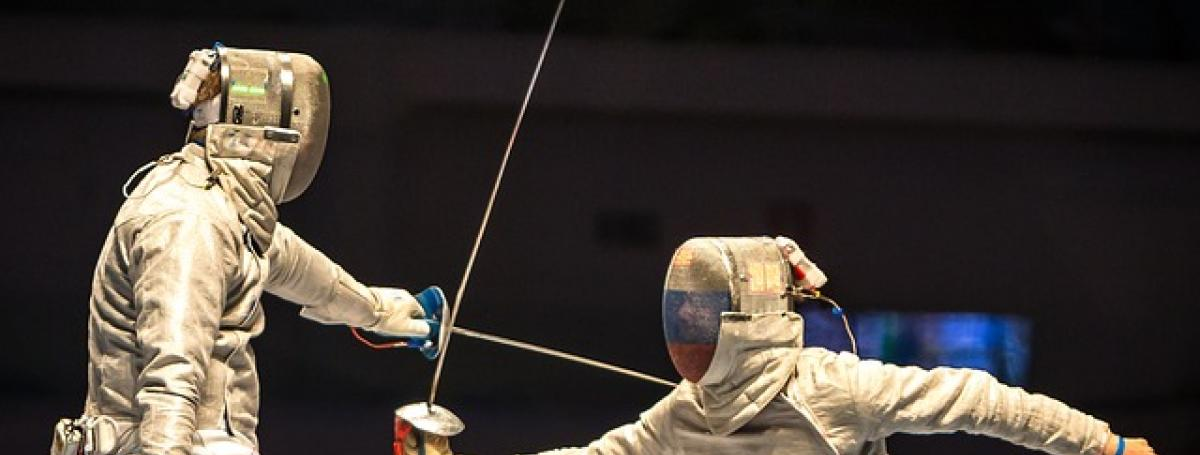A fencing match. Two people wearing protective suits with their swords drawn.