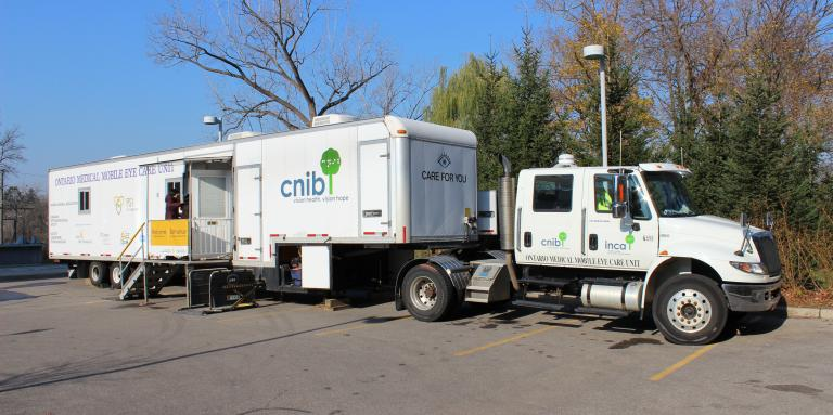 The CNIB eye van. A large white truck with a white trailer attached - featuring the CNIB logo.