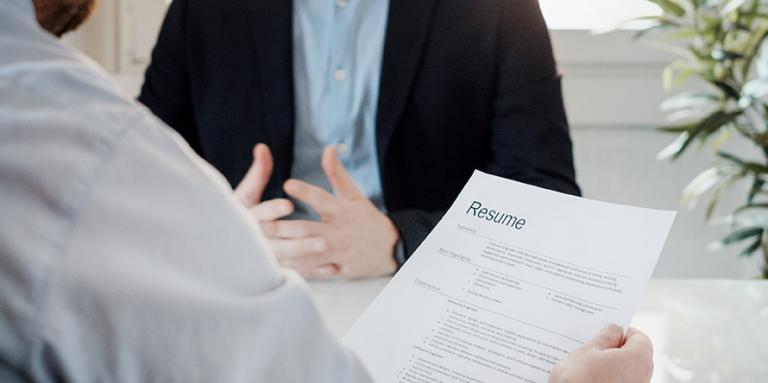 A recruiter holds a resume and interviews a candidate.