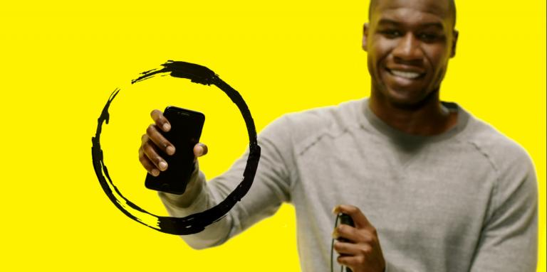 A man holding a smartphone. The phone is surrounded by a black swirl