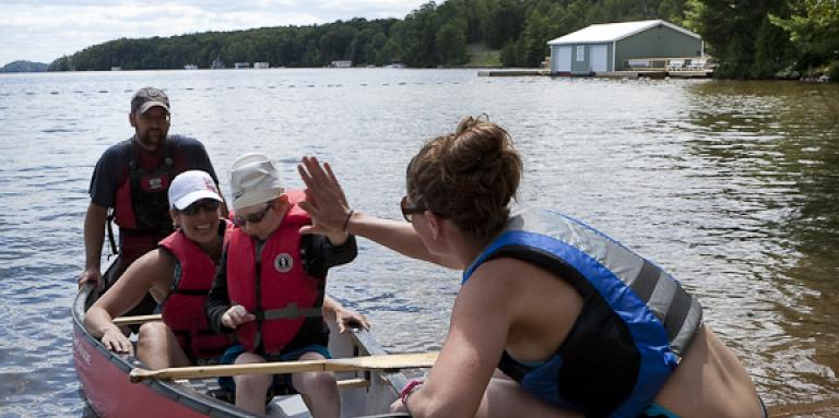 A group of campers in a canoe. one high fives a camp lead.