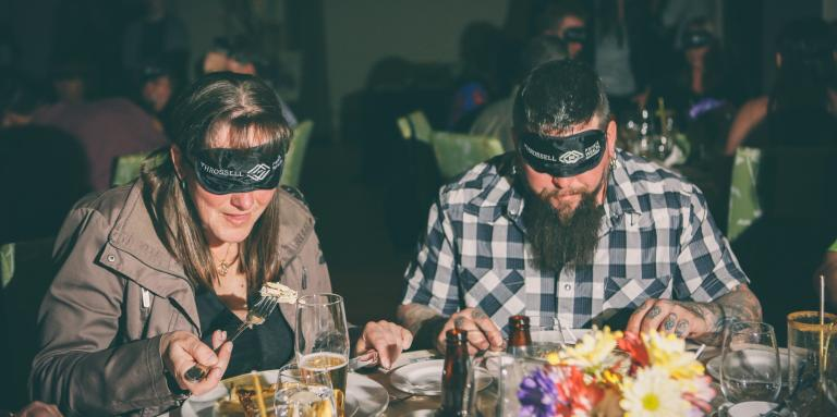 Two diners enjoying a meal with blindfolds on.