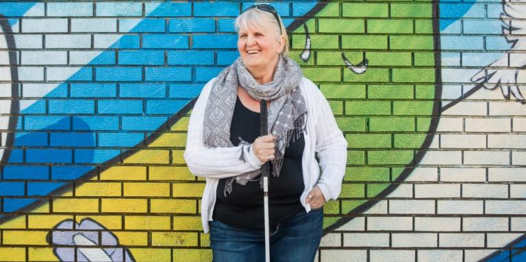 Wendy, holding her white cane, stands in front of a brick wall with a colourful mural.