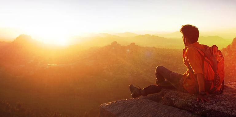 A man sits on the edge of a cliff, looking at the sun rise.