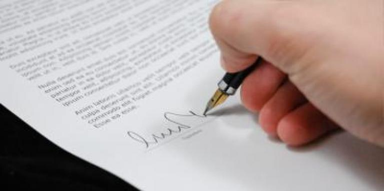 A hand signing a document.
