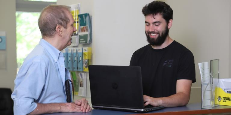 A CNIB volunteer and participant smile as they work on a laptop