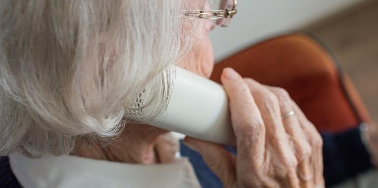 An elderly woman holds a landline telephone to her ear.