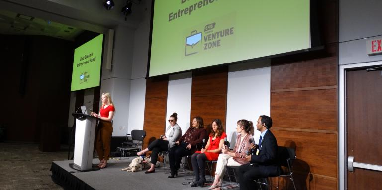 "A group of panelists sits on stage at Connecting the Dots. Behind them is a slideshow screen which displays ""Bold Dreams - Entrepreneur Panel."""
