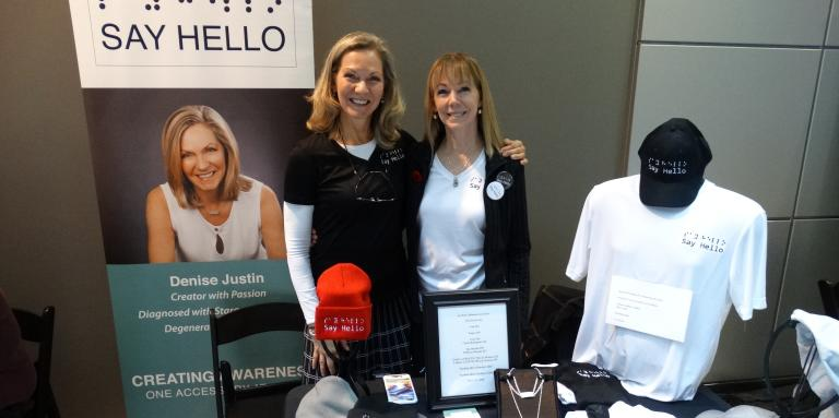 Two women stand behind an exhibitor table at Connecting the Dots in Toronto