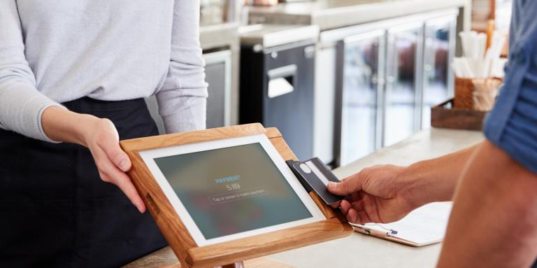 A person out of frame tapping their bank card on a touchscreen payment terminal, being presented by a café employee.