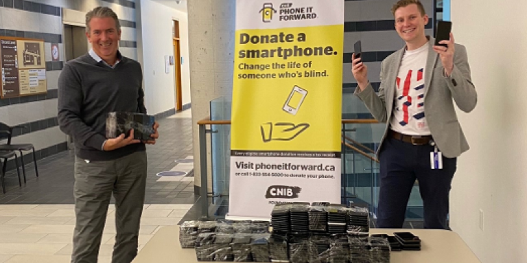 A smiling John M. Rafferty & Thomas Simpson stand at a table and hold multiple donated smartphones from the Bank of Canada. The table is also stacked with donated smartphones. Behind them stands a Phone it Forward banner display.