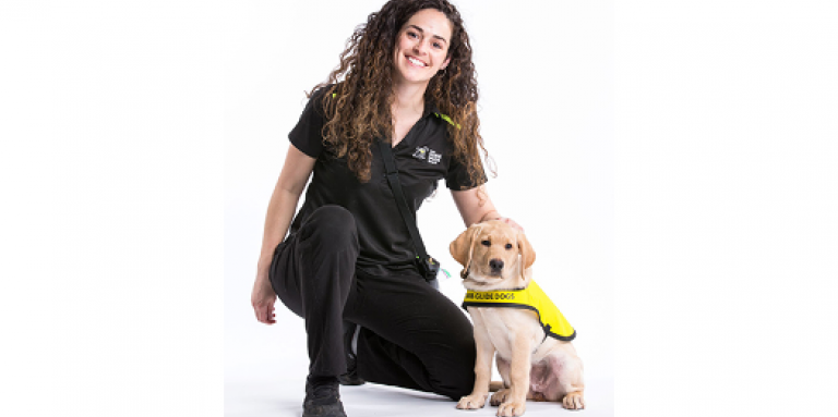 CNIB Guide Dogs trainer kneels next to puppy wearing yellow vest