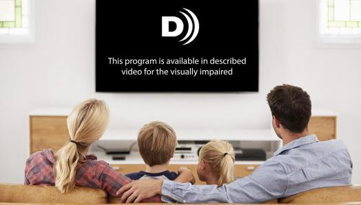 A family of four sit on the couch watching a television. The television reads: This program is available in described video for the visually impaired.