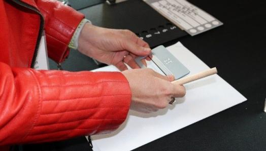 A woman holds a signature guide over a white page with a ballot and tactile ballot overlay beside her.