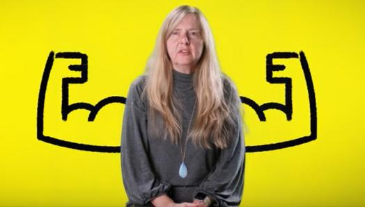 A woman in front of a yellow background with a cartoon drawing of flexed arms on either side of her.