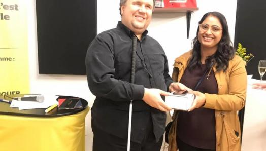 Aakruti Patel of West Groupe presents an iPhone to Sébastien Bolduc at the CNIB Montreal Hub.