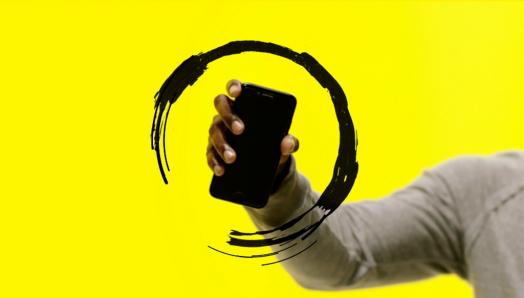A hand holds a smartphone up in the air. The phone is surrounded by an illustration of a circular black swirl.