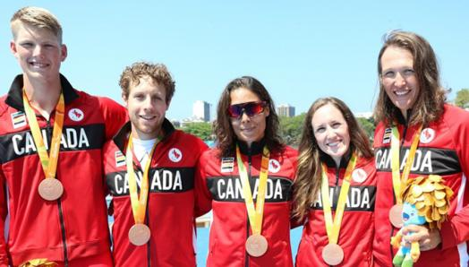 Victoria, along with two men and two women, wearing Team Canada Jackets and bronze medals.