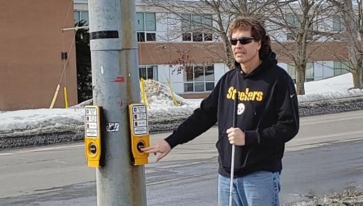 Bill Liggins stands on the corner at an Accessible Pedestrian Signal. He is holding his white cane in his left hand and pressing the crosswalk button with this right hand.