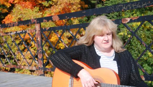 Photo of Christine playing guitar on a bridge. Trees are behind her and the sun shining.