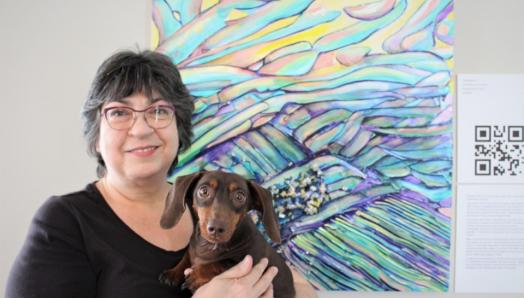 Robyn Rennie poses for a photo in front of her colourful artwork next to a digital printed QR Code. She is holding a small, chocolate-brown dog.