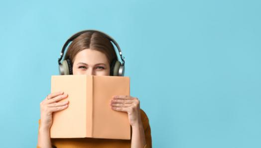 A young woman wears a pair of headphones and holds a book up to her face. The book is blocking her nose and mouth so only her eyes appear.