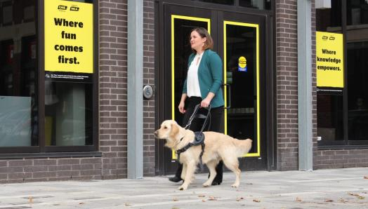 Erin Malone and her golden retriever guide dog, Winston, walking in front of a CNIB.