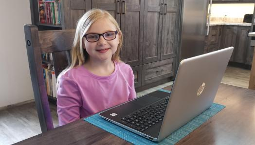 Madelyn sits in front of her laptop and smiles.