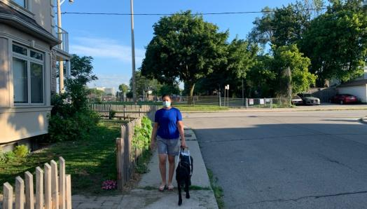 Victoria Nolan and her guide dog, Alan, walking along a sidewalk on a sunny day. Victoria is wearing a face mask.