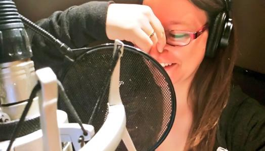 Dana sits in a recording booth and narrates a book. She is plugging her nose with her right hand to imitate an animated character voice. She is wearing big headphones and speaking into a microphone.