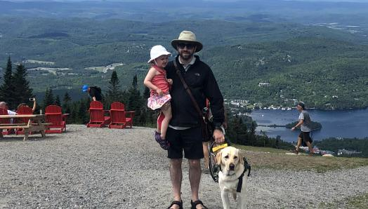 David with his daughter in one arm and his guide dog, Lilo's, harness in his other hand, smiling for the camera on Mont Tremblant overlooking Versant Sud, QB