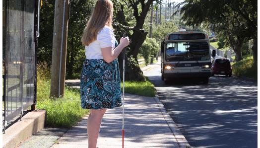 A woman holding a white cane standing at a bus stop waiting for the bus to pull up.
