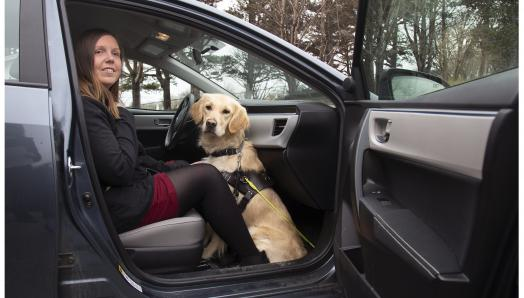 Kelly and her guide dog Maple, sitting in the passenger side of a car with the door open – smiling for the camera.