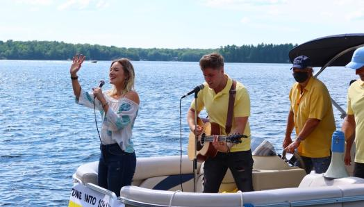 Leah Daniels singing and waving with Will Hebbes beside her playing guitar on a party pontoon, entertaining docks guests on Lake Muskoka.