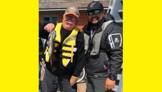 Bruce Roulston posing with a caught fish on a dock beside Eugene Chong at CNIB Lake Joe. They are both wearing life jackets and a ballcap.