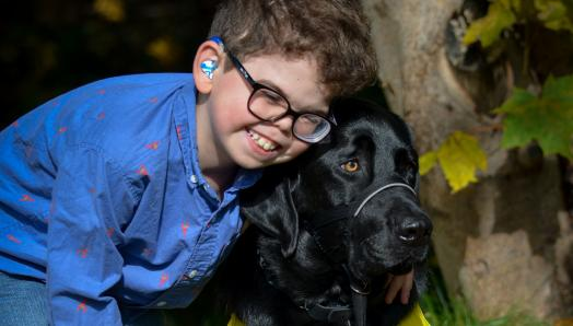 10-year-old Kaiden smiling and leaning down to embrace his CNIB Buddy Dog, Flinn, a black Labrador-Retriever cross.