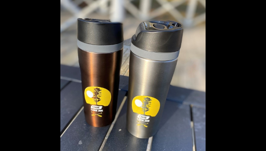 Bronze and charcoal coloured stainless steel travel mugs, with black lids on a table at camp.
