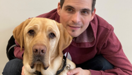 Ryan Hooey is crouched behind his Golden Labrador guide dog, Joe.