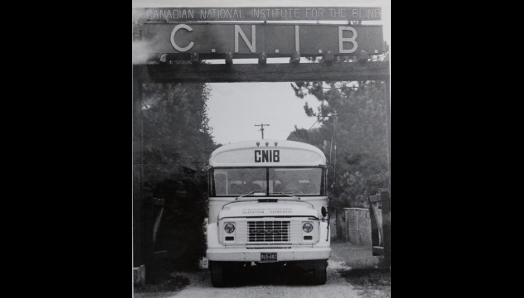 "A black and white photograph of an old school bus with ""CNIB"" on the front, driving under the ""CNIB"" welcome signage at Lake Joe."
