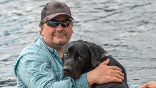 Photo of Tim and his guide dog Harlow, sitting in a boat with the water in the background.